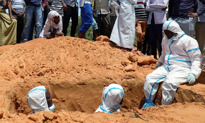 Somali workers in protective suits stand inside a grave in Mogadishu. Photograph: Feisal Omar/Reuters