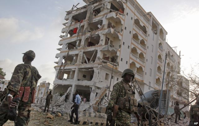 An African Union (AU) soldier walks past the scene of destruction following a suicide car bomb attack in the capital Mogadishu, Somalia, July 26, 2015.