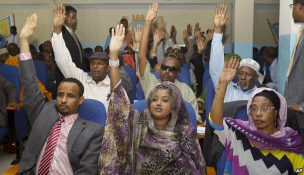 FILE - Somalia lawmakers raise their hands during a confidence vote on Prime Minister Abdiweli Sheikh Ahmed, at the Parliament Building in Mogadishu, Somalia, Dec. 6, 2014.