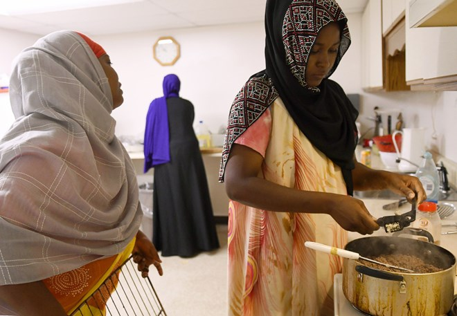Women prep deep-fried sambusas at the Viles Arboretum kitchen in Augusta for the Beyond Borders Farmers Market. Khadija Hussein, left, Asli Hassan and Farhiya Ibrahim serve the traditional Somali food at the market run by refugees who have resettled in Maine. Staff photo by Andy Molloy