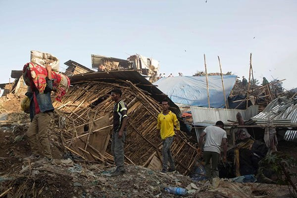 People move their belongings after dwellings built near the main landfill of Addis Ababa on the outskirts of the city were damaged in a landslide on march 12, 2017. PHOTO | ZACHARIAS ABUBEKER | AFP.
