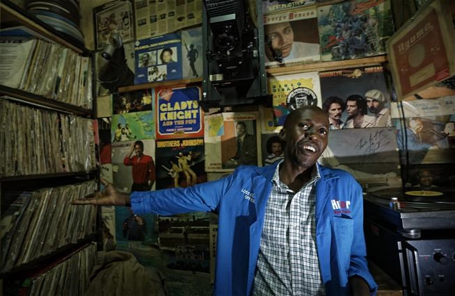 "In this photo taken Thursday, March 1, 2018, Ndegwa, 33, stands inside the vinyl records stall of his father James ""Jimmy"" Rugami, where he works in Kenyatta Market in Nairobi, Kenya.   (AP Photo/Ben Curtis)"