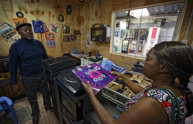 "In this photo taken Thursday, March 1, 2018, a potential customer discusses a record with James ""Jimmy"" Rugami inside his vinyl records stall in Kenyatta Market in Nairobi, Kenya.   (AP Photo/Ben Curtis)"