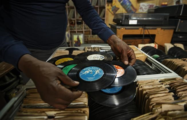 "In this photo taken Thursday, March 1, 2018, James ""Jimmy"" Rugami shows records inside his vinyl records stall in Kenyatta Market in Nairobi, Kenya.   (AP Photo/Ben Curtis)"