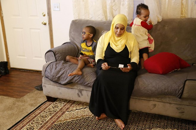 "Amina Olow, a refugee from Somalia, looks at photos of two of her eldest daughters while siting with two of her other children in her Columbus, Ohio, home on Friday, Feb. 23, 2018. The girls, Neemotallah, now 12, and Nastexo, now 9, live in Kenya with other family members. It has been 10 years since their mother has seen them. ""I never thought it would be this long,"" Olow says of her separation from her daughters, who she hopes can join her despite the fact that Somalia is on a list of countries impacted by the Trump administration travel ban. (AP Photo/Martha Irvine)"