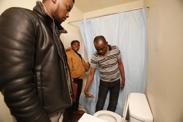 Ausa Emedi, right, examines a toilet in his family's new apartment in Columbus, Ohio, during the early morning hours of Thursday, Feb. 22, 2018, as his caseworker, Eric Rosingiza, explains to family members how it and shower work. The family of refugees from the Democratic Republic of Congo, including six children, had just flown to Columbus. The DRC has been plagued with political unrest and is not included in the Trump administration's travel ban. (AP Photo/Martha Irvine)