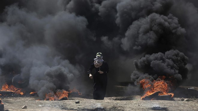 A Palestinian woman walks through black smoke from burning tires during a protest on the Gaza Strip's border with Israel on May 14, 2018.