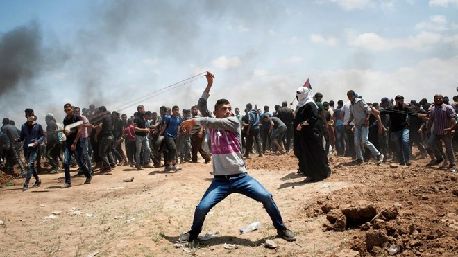 A Palestinian demonstrator throws a stone during a protest against the US Embassy move to Jerusalem and ahead of the 70th anniversary of Nakba, at the Gaza-Israeli border, in Abu Safia, Gaza Strip, May 14, 2018.
