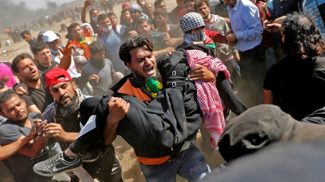 Palestinians carry a demonstrator injured during clashes with Israeli forces near the border between the Gaza strip and Israel east of Gaza City on May 14, 2018, as Palestinians protest over the inauguration of the US embassy following its controversial move to Jerusalem.