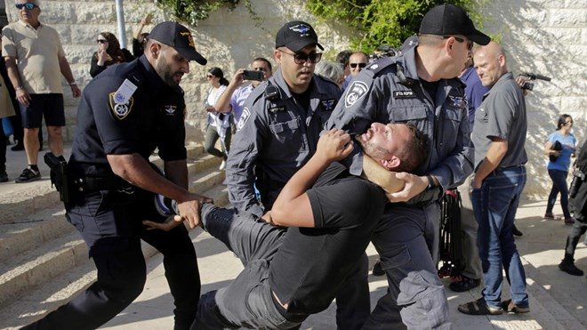 Israeli police officers detain a demonstrator during a protest outside the U.S. embassy in Jerusalem, during the embassy's official inauguration ceremony, Monday, May 14, 2018.