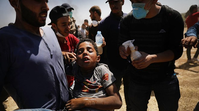 A child overcome by tear gas is rushed to medics at the border fence with Israel as mass demonstrations continue on May 14, 2018 in Gaza City, Gaza.